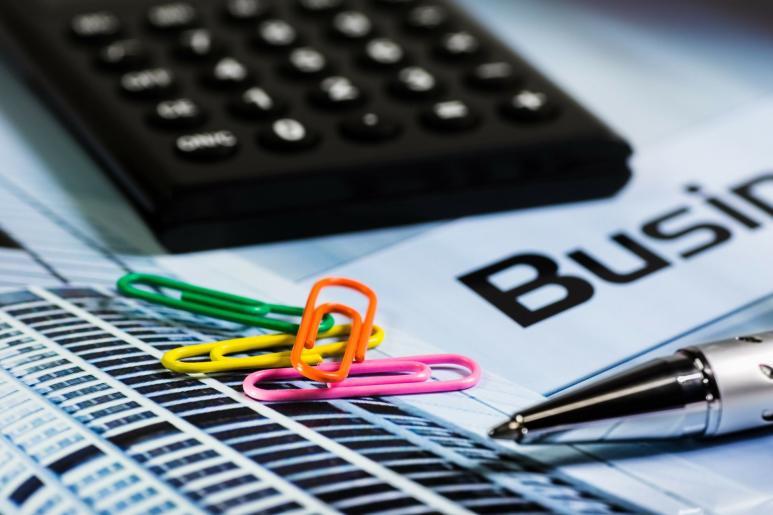Ein Bild von einem Taschenrechner, Büroklammern und dem Schriftzug Business